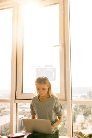 Photo for Young woman using laptop while sitting by window at home - Royalty Free Image