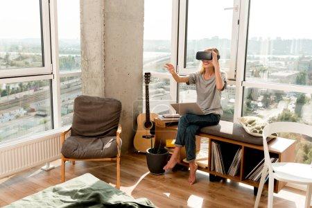 Photo pour Jeune femme en casque vr avec ordinateur portable assis à la fenêtre à la maison - image libre de droit