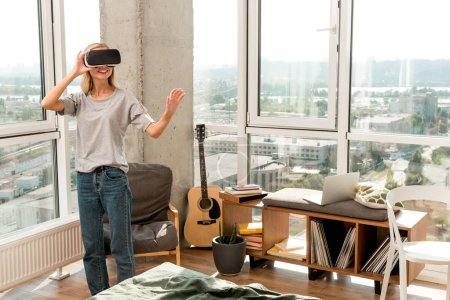 young cheerful woman in vr headset gesturing at home