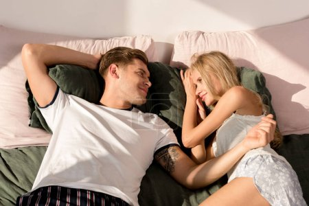 young couple in love in pajamas lying on bed in morning