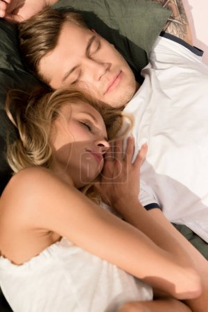 portrait of young couple sleeping in bed