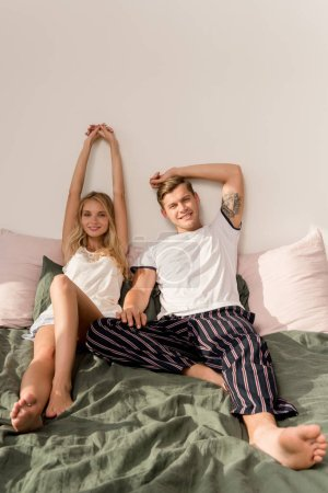 young loving couple in pajamas lying on bed at home in morning
