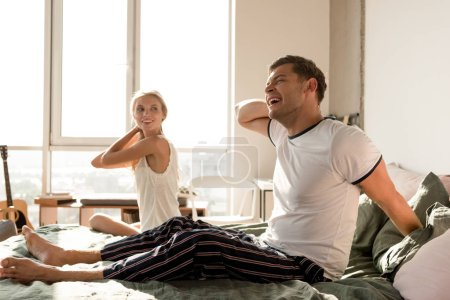 loving couple in pajamas sitting on bed at home in morning