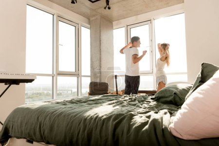 young couple in pajamas stretching at window at home in morning