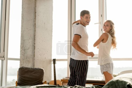 Photo for Young smiling couple in pajamas standing at window at home in morning - Royalty Free Image