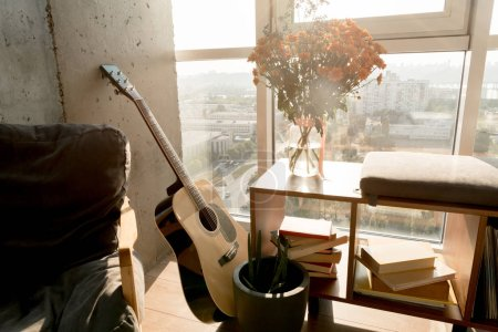 close up view of acoustic guitar and beautiful bouquet of flowers at window