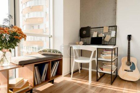 Photo pour Gros plan vue d'ordinateur portable avec écran blanc à la guitare acoustique et de la table près au bureau à domicile - image libre de droit