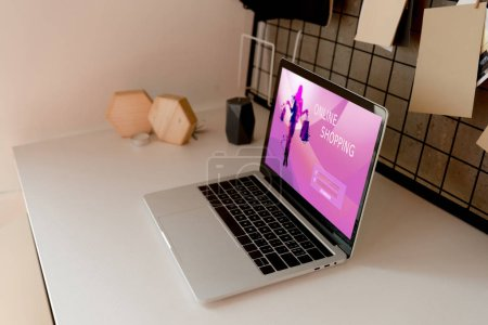 close up view of digital laptop with online shopping logo on screen on tabletop at home