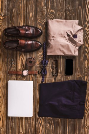Photo for Flat lay with masculine clothing, accessories and digital devices arranged on wooden surface - Royalty Free Image