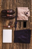 flat lay with masculine clothing, accessories and digital devices arranged on wooden surface