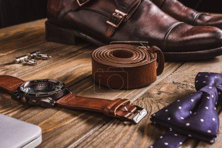 Photo pour Bouchent la vue des accessoires masculins en cuir et des chaussures disposées sur une table en bois - image libre de droit