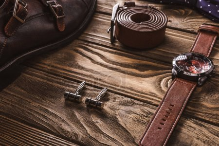 close up view of leather male accessories and shoes arranged on wooden tabletop