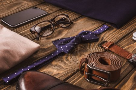 close up view of fashionable male clothing, accessories and smartphone on wooden surface