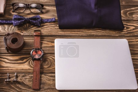 close up view of fashionable male accessories and laptop arranged on wooden surface