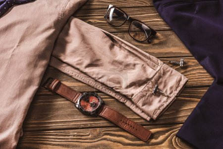 Photo for Close up view of stylish clothing, eyeglasses and wristwatch on wooden surface - Royalty Free Image