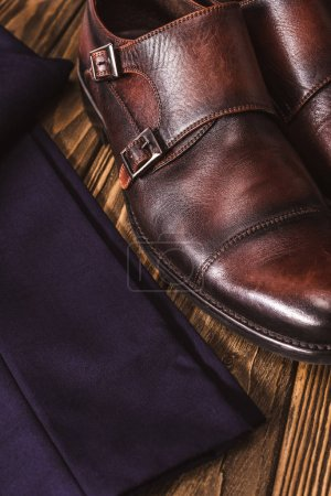 close up view of masculine leather shoes and pants on wooden tabletop