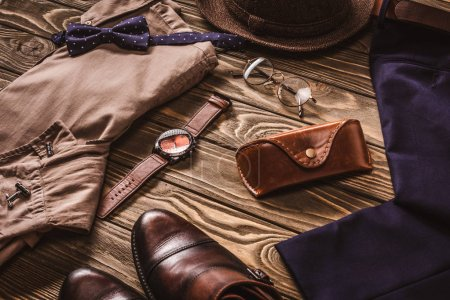 close up view of arrangement of masculine fashionable clothing and accessroies on wooden tabletop