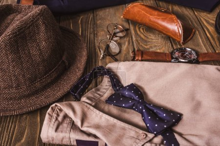 close up view of arrangement of masculine shirt and accessroies on wooden tabletop