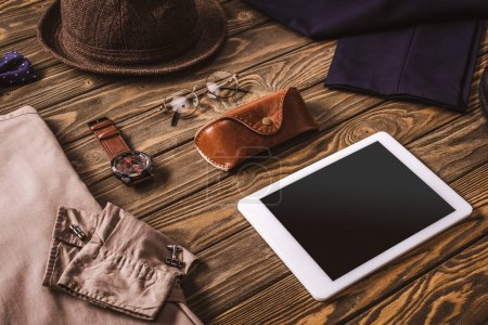close up view of male accessories, stylish clothing and tablet on wooden tabletop