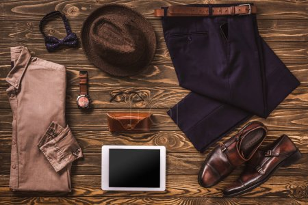 flat lay with masculine clothing, accessories and digital tablet arranged on wooden surface