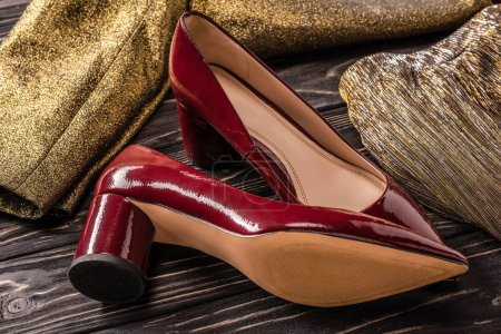 close up view of stylish red female shoes and golden clothing on wooden surface