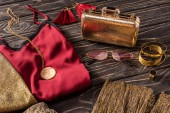 close up view of arrangement of golden and red fashionable feminine accessories and clothes on wooden surface