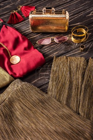 close up view of arrangement of golden and red fashionable feminine accessories and clothing on wooden surface