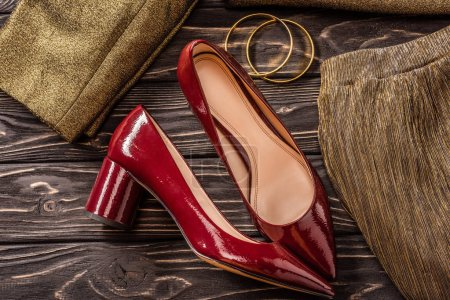 close up view of fashionable red and golden female shoes and bracelets on wooden tabletop