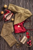flat lay with arrangement of fashionable feminine clothing, shoes and accessories on wooden surface