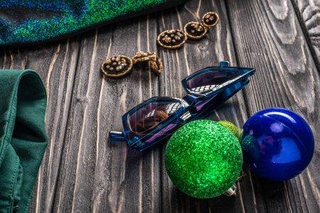 Photo pour Vue rapprochée de lunettes de soleil élégantes, boucles d'oreilles et boules de Noël sur table en bois - image libre de droit