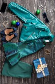 flat lay with feminine accessories, clothing, smartphone and earphones arranged on wooden tabletop