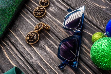 close up view of stylish sunglasses and earrings on wooden tabletop