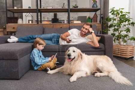 happy father watching tv on couch while his son using tablet on floor with golden retriever