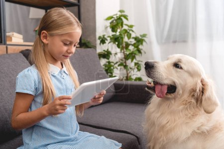 adorable little child with labrador dog using tablet while sitting on couch