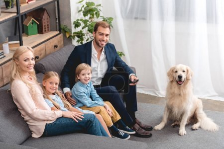 high angle view of happy young family sitting on couch at home with dog and looking at camera