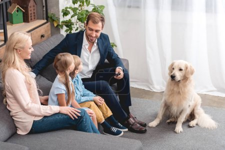 Photo for High angle view of happy young family sitting on couch at home with dog - Royalty Free Image