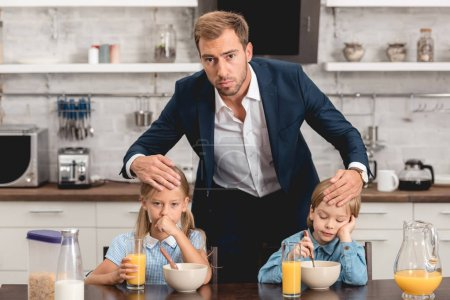 father checking temperature of his sick kids by touching their foreheads during breakfast and looking at camera