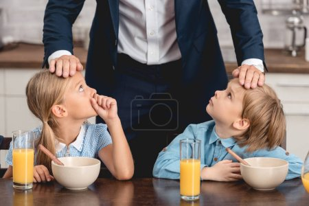 cropped shot fo father checking temperature of his sick kids by touching their foreheads during breakfast