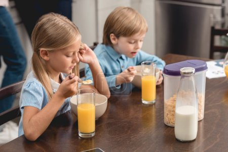 cute little kids having cereal for breakfast together at kitchen
