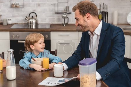 Photo for Father and son laughing together at kitchen during breakfast - Royalty Free Image