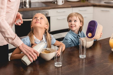 cropped shot of mother pouring milk into cereal for happy little kids during breakfast