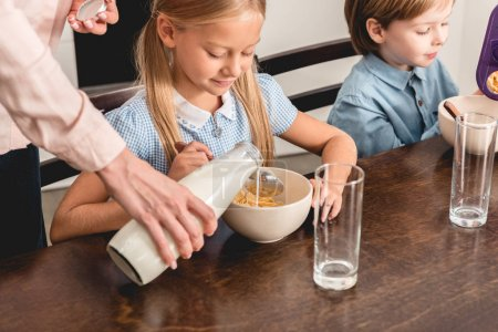 cropped shot of mother pouring milk into cereal for kids during breakfast