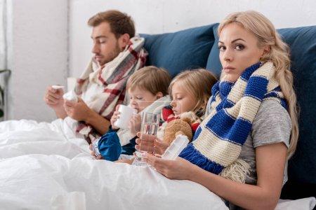 Foto de Familia joven enferma sentada en la cama junto con varios métodos de tratamiento - Imagen libre de derechos