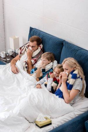 Photo pour Vue grand angle de la jeune famille malade soufflant nez avec des serviettes ensemble tout en étant couché dans le lit - image libre de droit