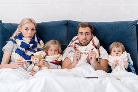 sick young family in scarves holding electric thermometers and looking at camera while lying in bed