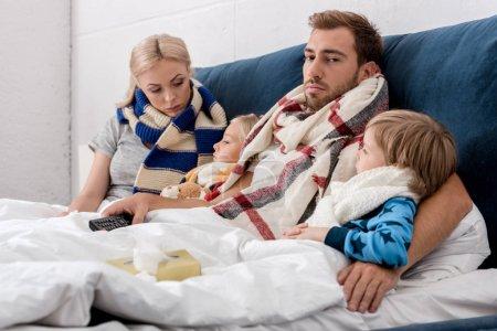 Photo pour Malade jeune famille dans les écharpes couché dans le lit avec tv télécommande - image libre de droit