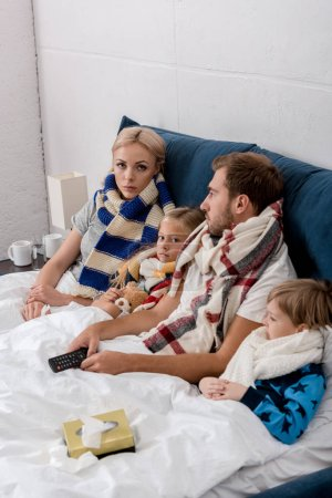 sick young family in scarves lying in bed together