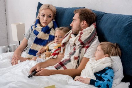 sick young family in scarves looking at each other while lying in bed