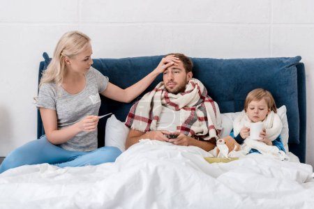 woman checking temperature of sick husband and son while they lying in bed