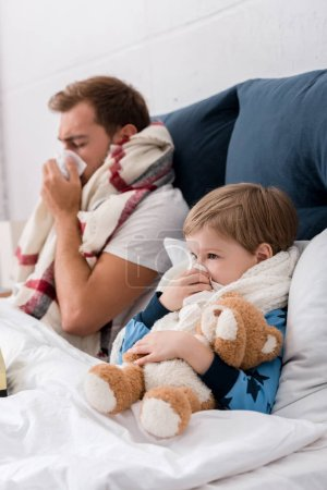young father and son blowing noses with paper napkins while lying in bed
